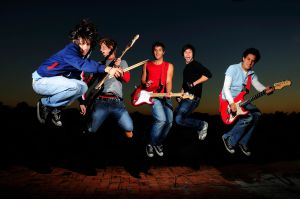 a music band and each member is holding a guitar