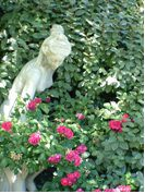statue of a woman leaning down to smell the roses planted around her