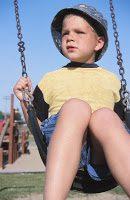 sad young boy on a swing