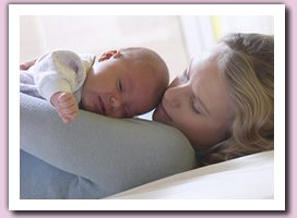 mother holding newborn and thinking