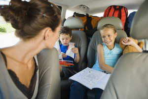 mom checks on kids seated in car