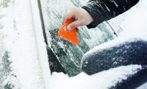 scraping ice and snow from car windshield