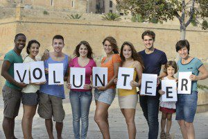people holding up the letters that spell volunteer