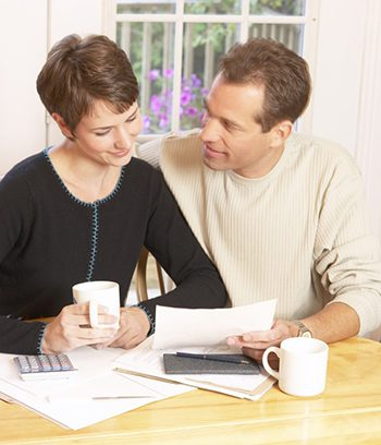 couple working on finances together at the table with coffee