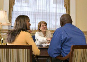 couple avoid financial mistakes sitting with financial advisor shaking hands