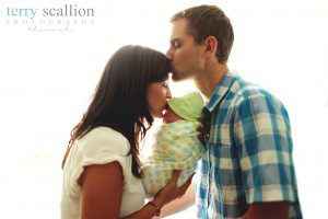 couple kiss their newly adopted baby