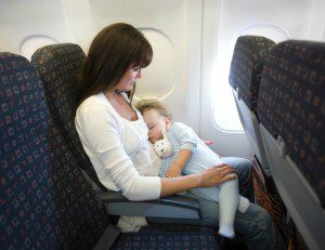 mom holding sleeping baby on an airplane