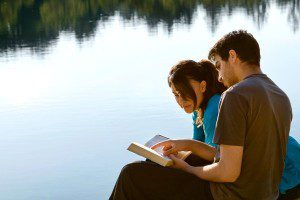 young Christian couple reading a Bible together to strengthen their marriage