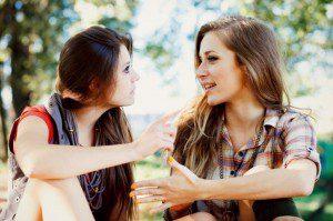 two women friends talking together outside