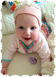 baby girl smiles at the camera belonging to a family's steps to adoption
