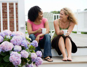 two women talk on front porch steps about adoption