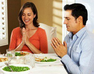 couple praying together at mealtime