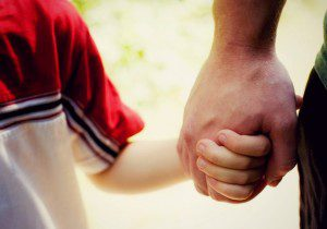 child and parent holding hands on a walk