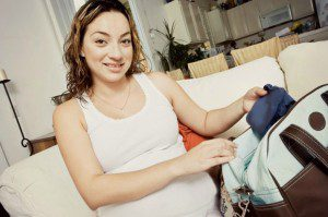pregnant woman packing a bag for the hospital