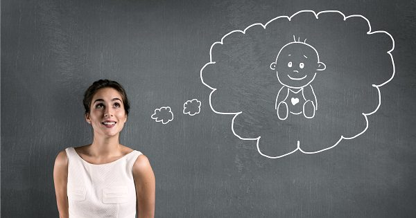 Woman stands in front of a chalkboard. A thought bubble sketched behind her with a sketch of a baby inside it
