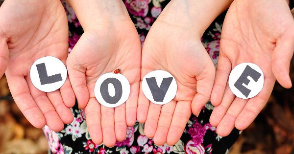 love spelled out across a group of hands