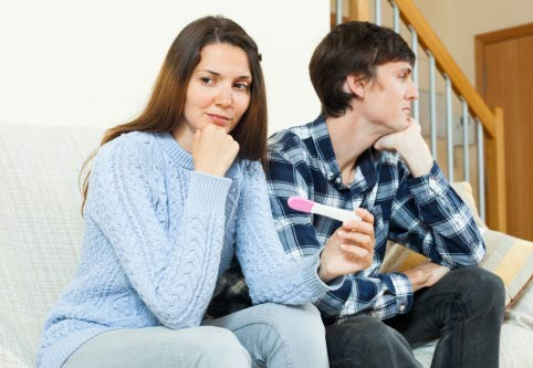 Woman and man sitting on a sofa, woman holding a pregnancy test