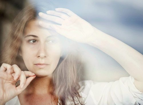 Woman looking outside her window, thinking