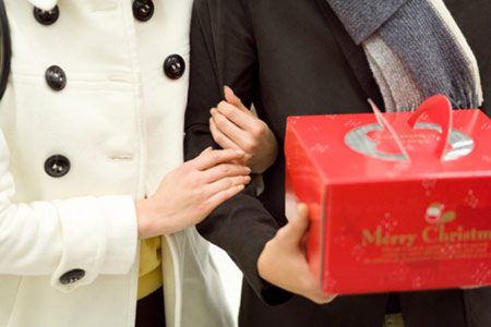 Cropped photo of a couple, husband carrying Christmas present