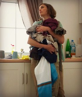Woman holding a large load of laundry