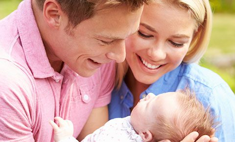 Happy Caucasian couple gaze at their baby
