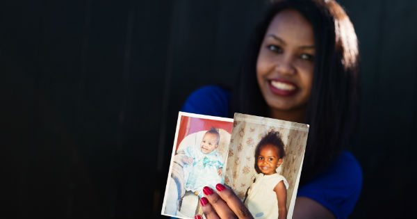 Young mixed-race woman holds up photos of her infant daughter