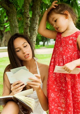 Young mother and her daughter outside looking at photos