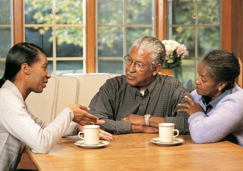 An adult woman talks with her parents over coffee