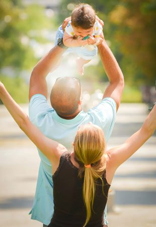 Joyful adoptive parents outdoors, dad lifts the child up in the air