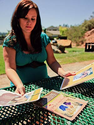 An expectant mother sits at a picnic table as she looks at adoption profiles
