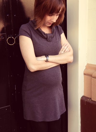 Pregnant woman standing outside, arms crossed