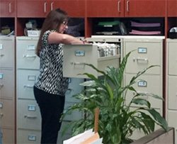 A woman retrieves a profile from a file cabinet