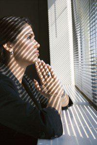 Woman leaning on windowsill praying