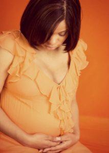 Portrait of a bi-racial pregnant woman, looking down