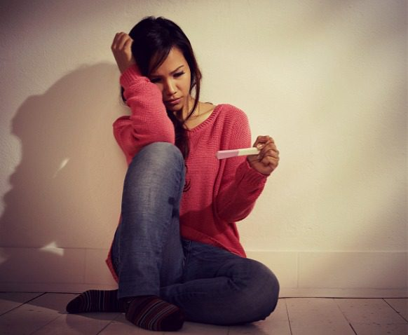 Young woman sitting on the floor, looking at a pregnancy test with fear