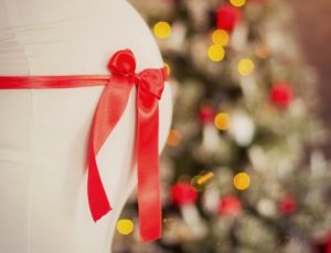 Close-up of a pregnant woman's belly with a red ribbon around it. Christmas tree in background