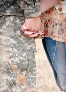 Close up of a member of the military holding his wife's hand