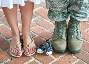 Military couple posing with baby shoes