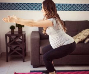 Pregnant woman performs a squat in her living room