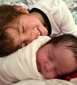 young boy snuggles with his newly adopted baby sibling