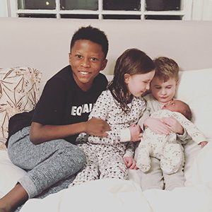 Happy adoptive family embrace their newest sibling