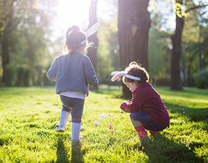 Two toddlers wearing bunny ears and playing with Easter eggs in a park lined with trees