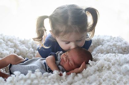 Young age Caucasian girl kisses her new adopted newborn age Bi-racial baby brother