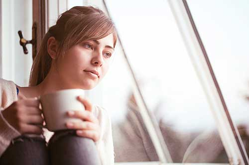 A young woman sits near a window holding a cup of coffee thinking about adoption
