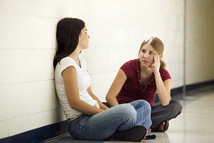 Two young Caucasian women sitting on the floor of a school discussing rape