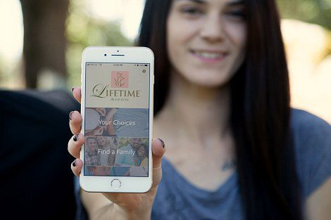 Woman holds out iPhone showing the app