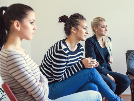Three young women at a birth mother support group meeting