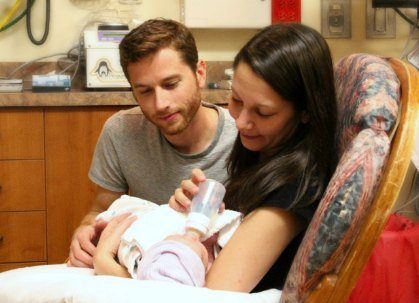 New adoptive parents gaze with wonder at their newborn baby girl