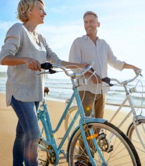 Caucasian couple biking on the beach