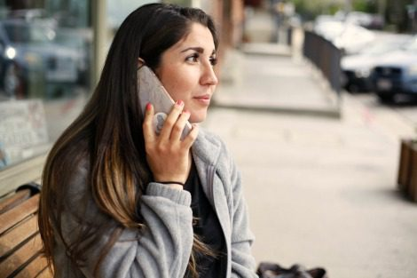 Woman talking on a cell phone, thinking of questions to ask adoptive parents